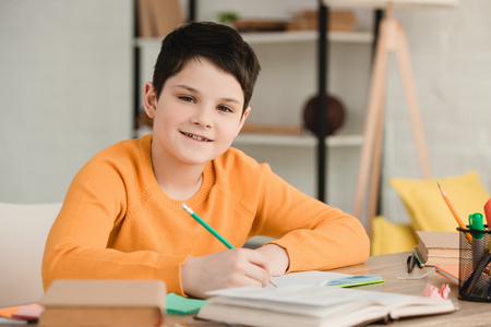 cute boy smiling at camera while sitting at desk and doing schoolwork at home Stock Photo