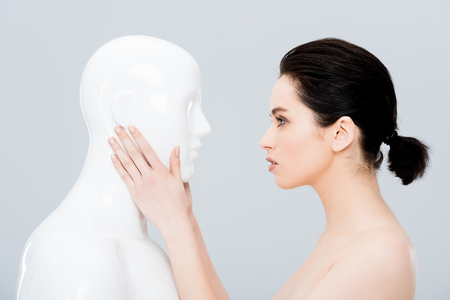 beautiful young woman touching plastic mannequin isolated on grey