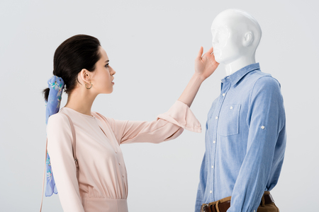 beautiful girl stroking mannequin isolated on grey Фото со стока