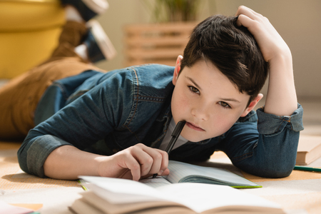 selective focus of thoughtful boy lying on floor near copy book while making schoolwork at home