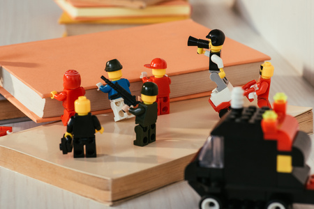 KYIV, UKRAINE - MARCH 15, 2019: plastic lego minifigures carrying book near guard figures with gun and mouthpiece Editorial