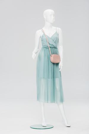 Plastikpuppe mit Tasche und Kleid isoliert auf grau