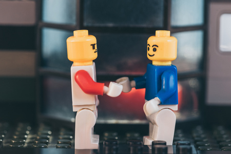 KYIV, UKRAINE - MARCH 15, 2019: yellow lego figurines with face expressions shaking hands Editorial