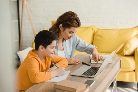 smiling mother helping attentive son doing schoolwork while sitting at desk with laptop at home