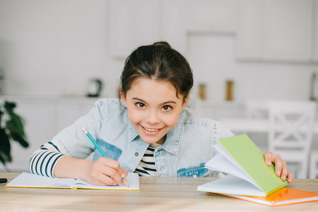 cheerful schoolchild smiling and looking at camera while doing schoolwork at home