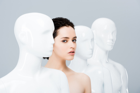 beautiful girl posing in row of mannequins isolated on grey