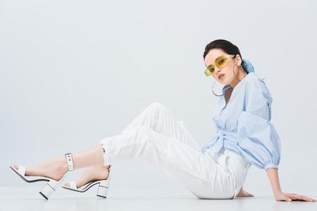 beautiful stylish girl in sunglasses sitting and posing on grey