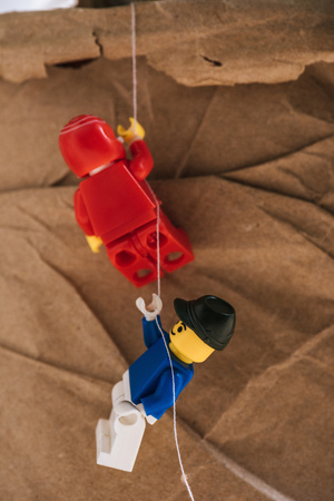 KYIV, UKRAINE - MARCH 15, 2019: close up view of red and blue plastic lego figurines climbing rope