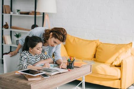schöne Frau, die der entzückenden Tochter hilft, zu Hause Schulaufgaben zu machen