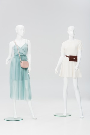 plastic mannequins with bags and dresses isolated on grey Stock Photo