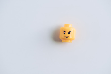 KYIV, UKRAINE - MARCH 15, 2019: top view of lego figurine head with angry face on white with copy space