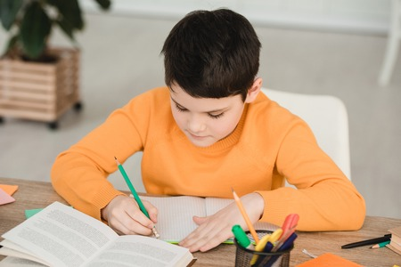 attentive boy reading book and writing in copy book while doing schoolwork at home
