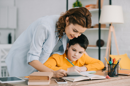 pretty smiling woman helping adorable son doing schoolwork at home Imagens