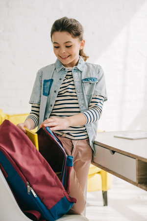 adorable smiling child packing back pack while standing near desk at home
