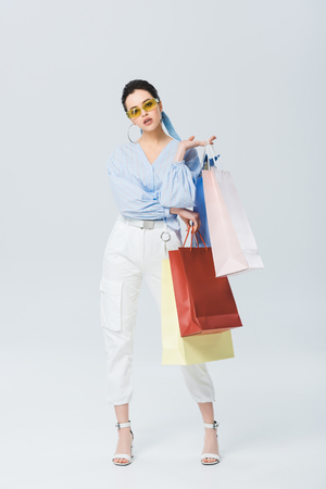 beautiful stylish girl with shopping bags on grey