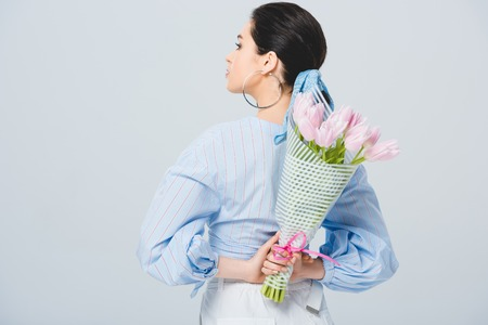 Back view of stylish girl with bouquet of tulips isolated on grey