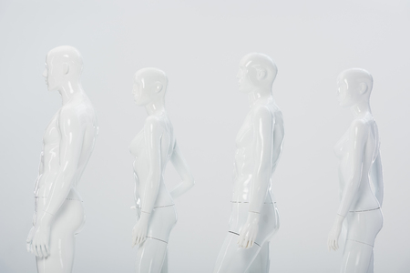 white plastic dummies in row isolated on grey