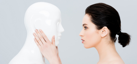 panoramic shot of beautiful young woman touching plastic mannequin isolated on grey