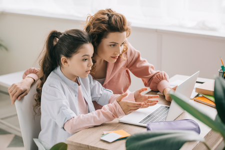 beautiful mother helping adorable daughter doing schoolwork at home