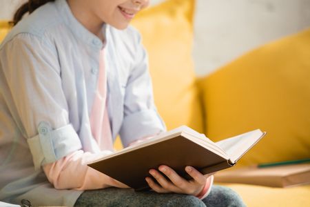cropped view of smiling child reading book while sitting on sofa at home Stock Photo