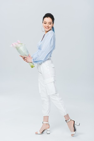 beautiful stylish girl with bouquet of tulips smiling on grey Stok Fotoğraf