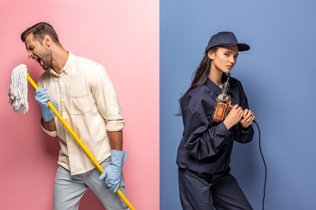 man in rubber gloves singing with mop and woman in construction worker uniform with drill on blue and pink