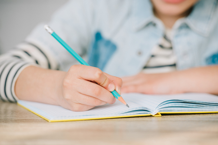 partial view of schoolkid writing in copy book while doing homework