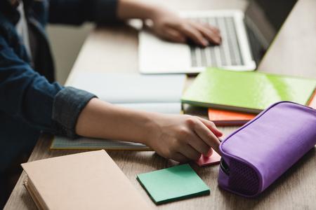 Ausgeschnittene Ansicht eines Schülers, der Laptop benutzt, während er mit Kopierbüchern am Schreibtisch sitzt und Hausaufgaben macht