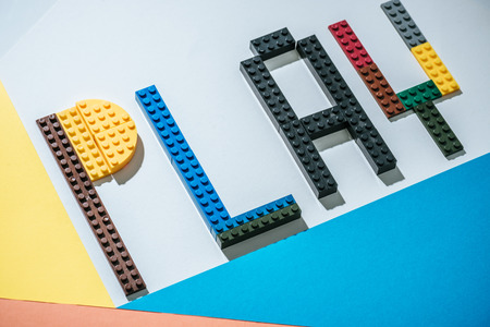 KYIV, UKRAINE - MARCH 15, 2019: word play made of colorful lego blocks on geometrical background 報道画像