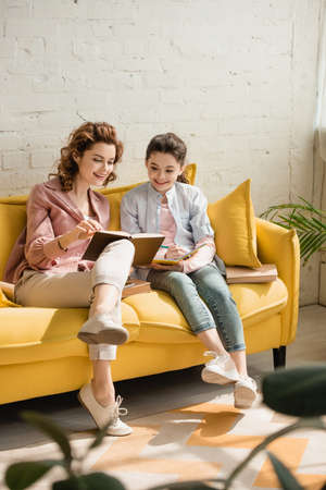 cheerful mother and daughter sitting on yellow sofa and reading book together Stock Photo