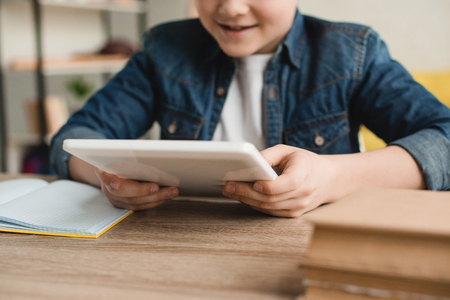 partial view of smiling boy using digital tablet while sitting at desk with books at home Stock Photo