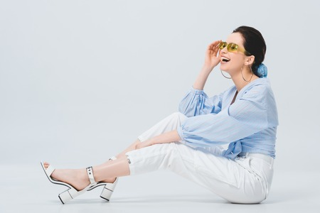 beautiful stylish girl in sunglasses posing and laughing on grey Фото со стока