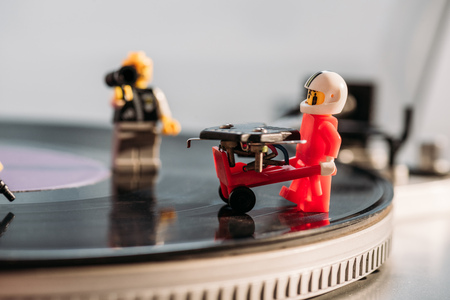 KYIV, UKRAINE - MARCH 15, 2019: selective focus of plastic lego figurine with toy trolley on vinyl record player