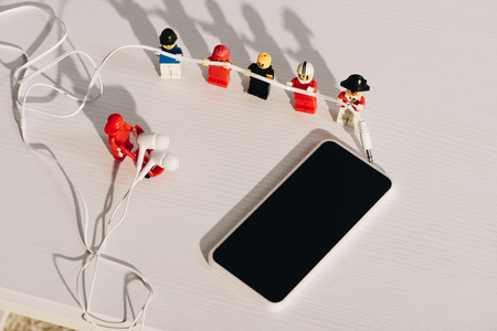 KYIV, UKRAINE - MARCH 15, 2019: lego figurines holding earphones near smartphone with blank screen on white table Reklamní fotografie