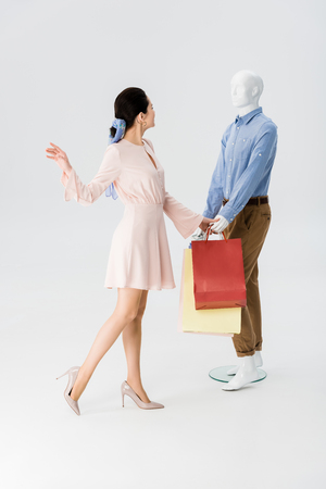 beautiful girl gesturing near mannequin with shopping bags on grey