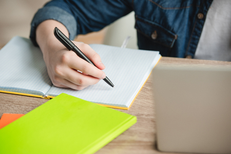 cropped view of schoolboy writing in notebook while doing schoolwork at home