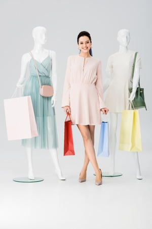beautiful smiling young woman with shopping bags near mannequins on grey Stock Photo