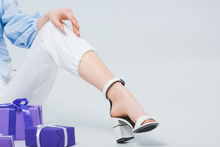 Cropped view of stylish girl in pants and sandal sitting near gift boxes on grey 版權商用圖片