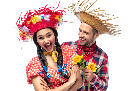 man and excited young woman in festive clothes with sunflowers isolated on white