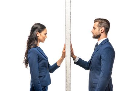 Geschäftsmann und Geschäftsfrau in Anzügen getrennt durch Wand isoliert auf weiß