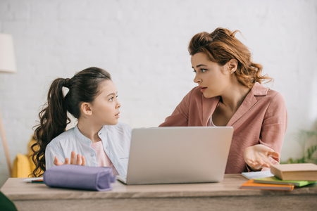 discouraged woman showing shrug gesture while using laptop together with daughter Stock Photo