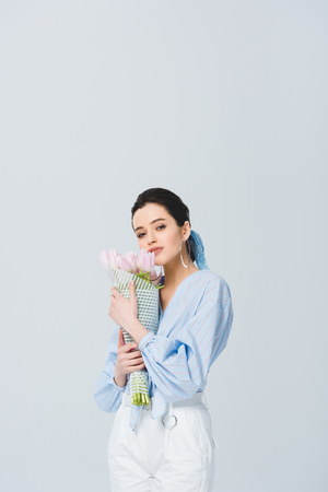 beautiful stylish girl with bouquet of tulips isolated on grey