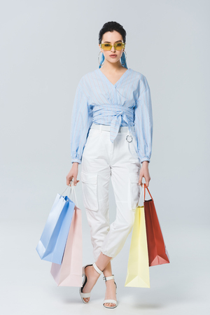 beautiful fashionable girl with shopping bags on grey