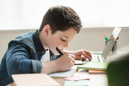 adorable attentive boy writing in notebook and using laptop while doing homework Stockfoto