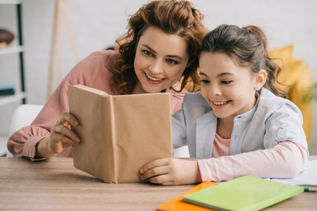 happy mother and daughter sitting at wooden table and reading book together Stock Photo