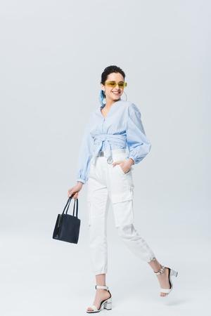 beautiful stylish girl walking and smiling on grey Фото со стока