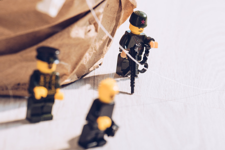 KYIV, UKRAINE - MARCH 15, 2019: lego policemen minifigures with gun and handcuffs on white table