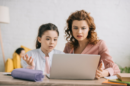 discouraged woman and daughter gesturing while using laptop together