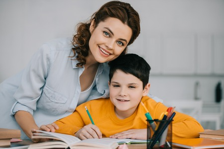 happy mother with adorable son smiling and looking at camera while doing homework together