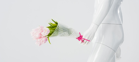 panoramic shot of mannequin doll with bouquet of tulips isolated on grey